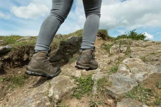 Close up of hiker's walking boots stomping across rocky ground