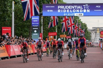 A group of cyclists crossing the start line at the Prudential RideLondon-Surrey 100.