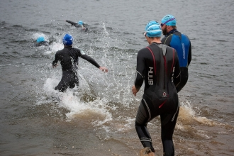 Wild swimmers entering Wimbleball Lake to take part in the Exmoor Open Water Swim