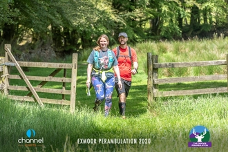 Two hikers walking through gates surrounded by woodland in Exmoor National Park.