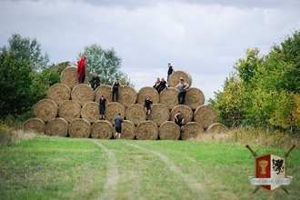 Participants scaling a huge wall of hay bales