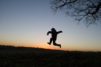 Young boy silhouetted at dusk playing on edge of woodland
