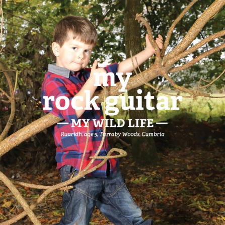 Ruaridh plays guitar on a tree branch