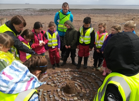Children creating a mandala on Dunster Beach as part of the Wild Beach programme